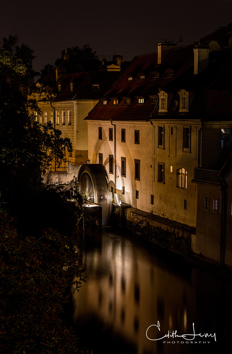 The Vltava river in Prague at night. This is a view from the Charles Bridge of a building with a water wheel at its side.