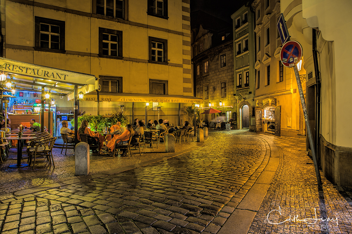 A cafe in the old city at night with a full crowd of diners enjoying a lovely fall evening.