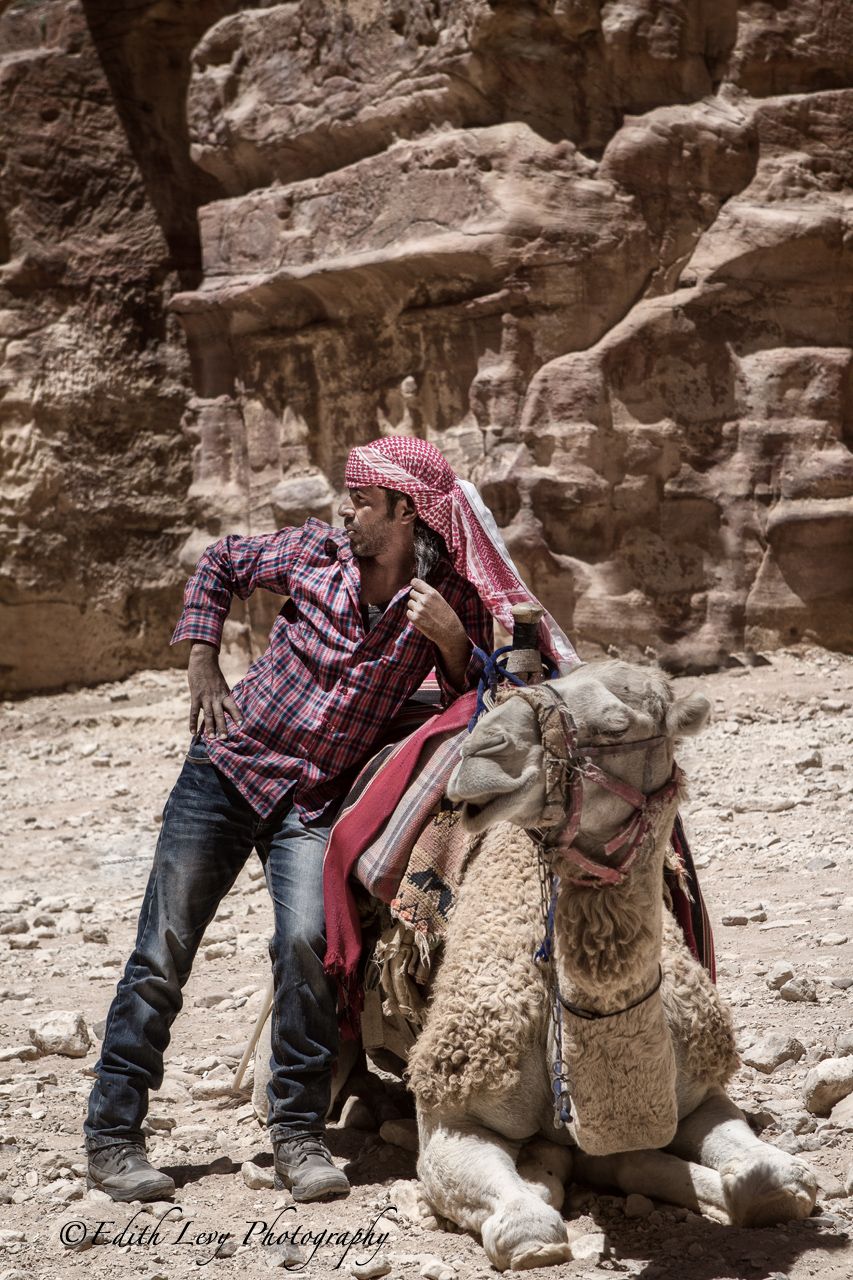 The Camel handler takes a break while waiting to give rides to the tourists.