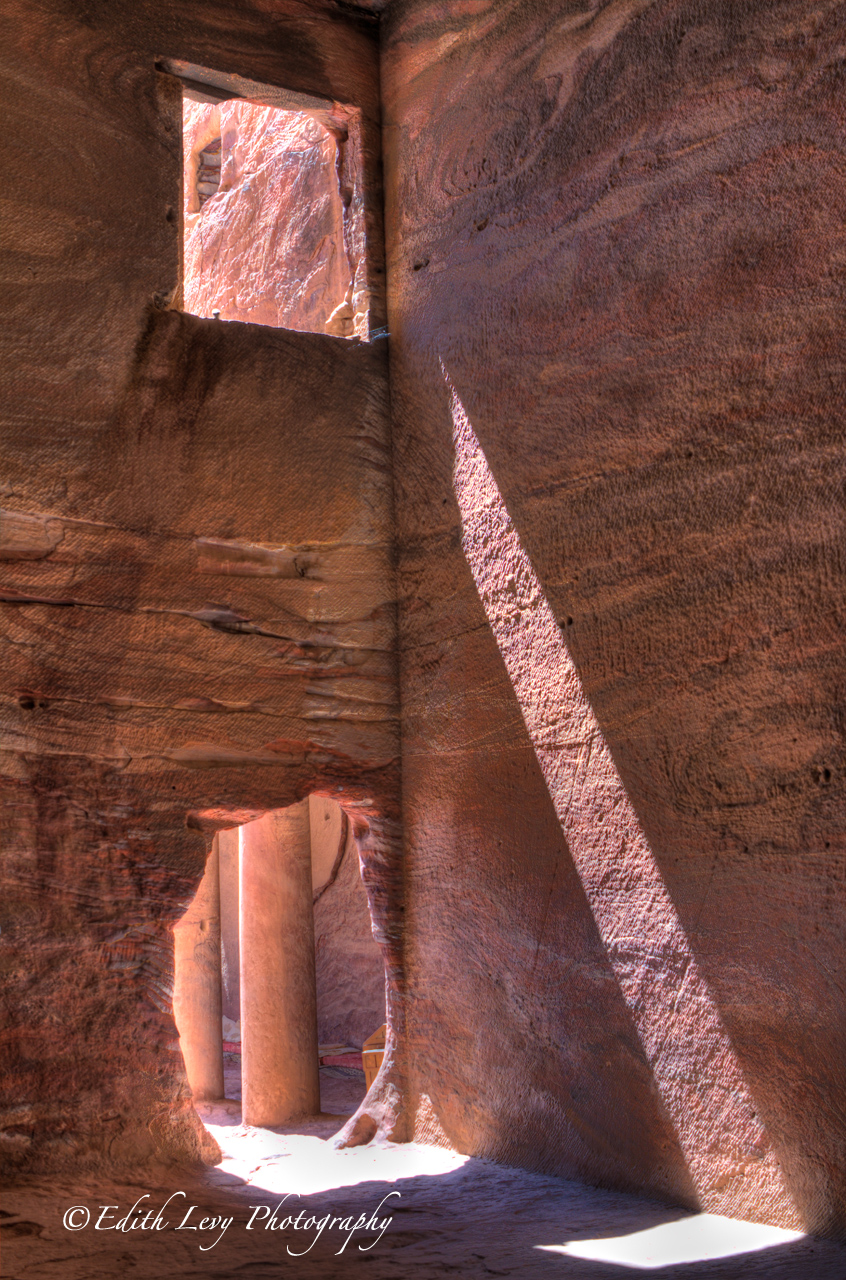 Sunlight streams through an opening into a tomb in Petra