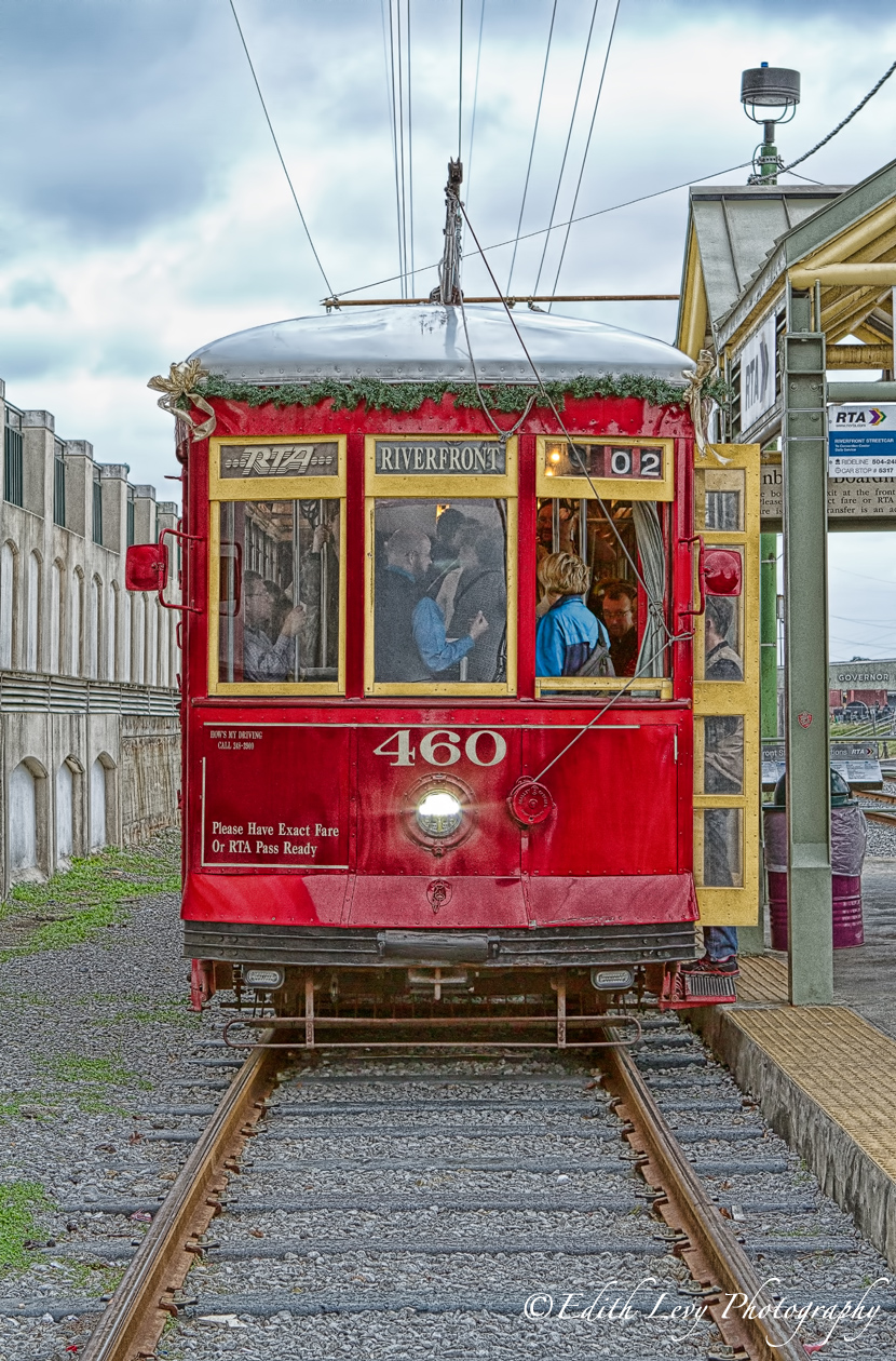 A bright red streetcar along the river front in New Orleans.