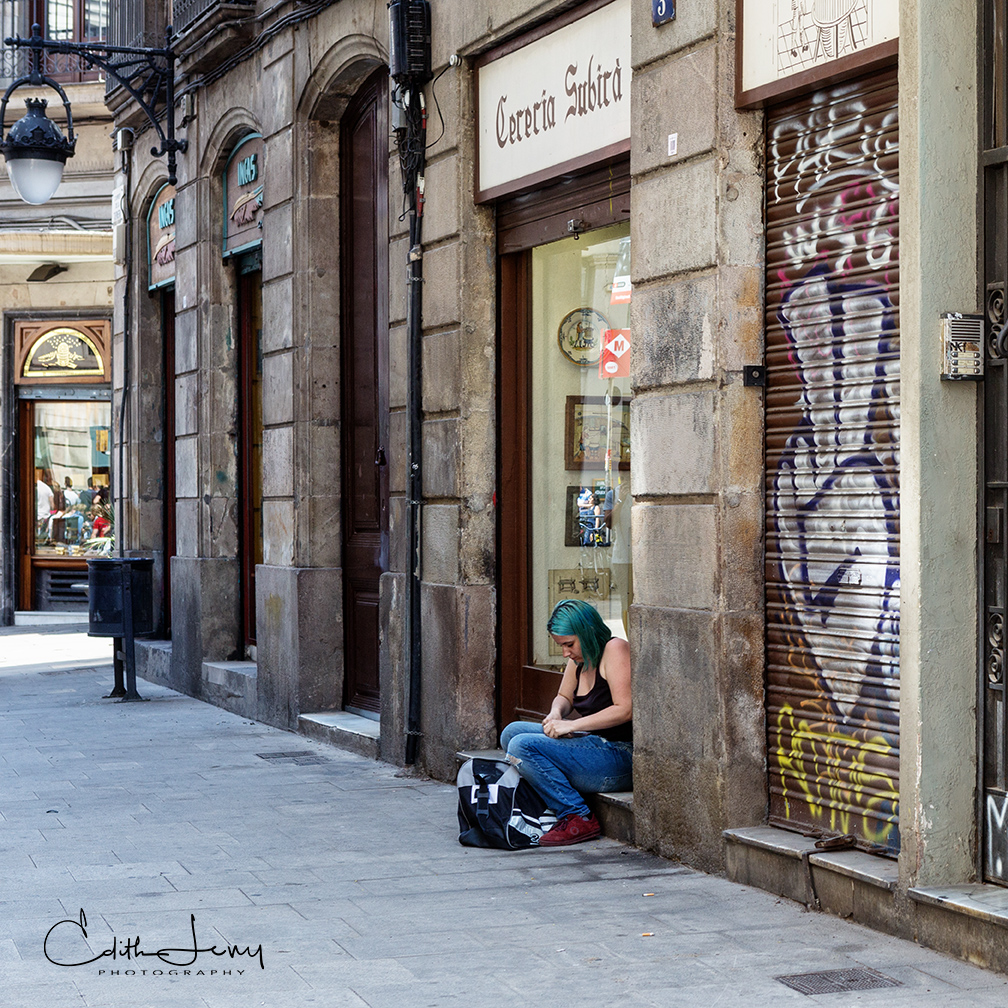 A girl with green hair takes a break on the streets of Barcelona.