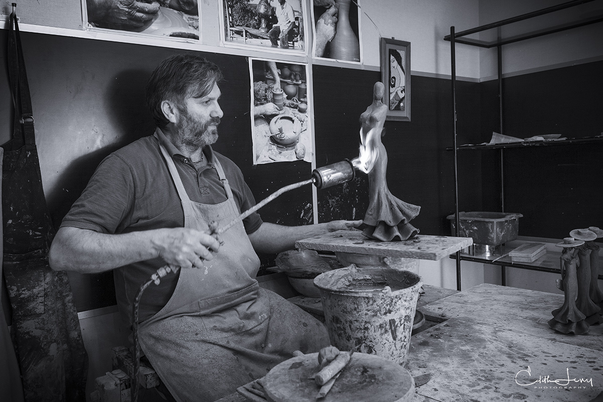 A Cordoba Artisan in his workshop creating a flamenco dancer on his pottery wheel.